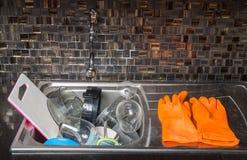 Um par de luvas de lavagem do prato alaranjado pendura em um surr do torneira do dissipador Fotografia de Stock
