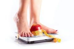 Um par de pés fêmeas que estão em uma escala de banheiro com appl vermelho Fotografia de Stock