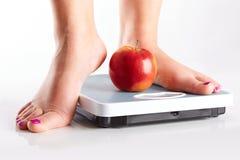 Um par de pés fêmeas que estão em uma escala de banheiro com appl vermelho Foto de Stock
