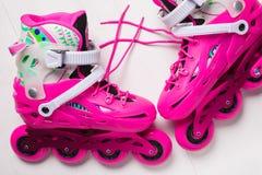 Um par de patins de rolo à moda cor-de-rosa em um fundo de madeira branco fotos de stock