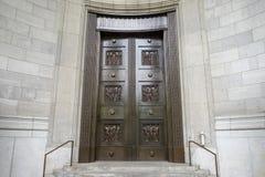Um par de portas de bronze velhas em uma entrada fotografia de stock
