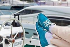 Um par de pés humanos nas calças e de topsiders azuis brilhantes no iate Imagem de Stock