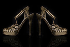 Um par de sandálias dos saltos altos do couro do ouro no fundo preto Fotos de Stock Royalty Free