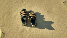 Um par de sand?lias na areia fotos de stock royalty free