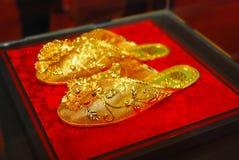 Um par de sapatas douradas Imagens de Stock