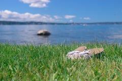 Um par de sapatas em uma grama verde-clara perto do lago Imagens de Stock