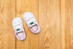 Um par de sapatilhas do bebê no fundo de madeira Foto de Stock Royalty Free