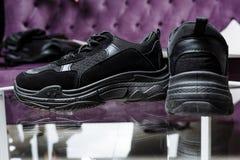 Um par de sapatilhas pretas no fundo de uma tabela de vidro e de um sofá roxo foto de stock royalty free
