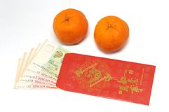 Um par de tanjerinas e de um envelope vermelho com notas do dinheiro de Singapura para dentro fotografia de stock