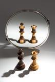 Um par de um rei preto e de uma rainha branca está olhando em um espelho para considerar-se como um par colorido preto e branco Imagens de Stock Royalty Free
