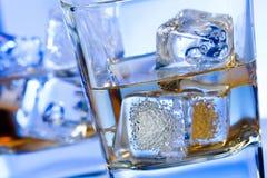 Um par de vidros da bebida alcoólica com gelo no azul do disco ilumina-se Foto de Stock Royalty Free