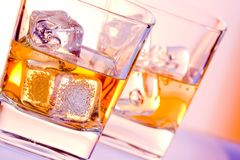 Um par de vidros da bebida com gelo na violeta do disco ilumina-se Fotografia de Stock