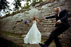Um par do casamento dança atrás de uma parede de pedra Imagem de Stock