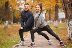 Um par dos esportes é contratado nos esportes no parque do outono que faz um exercício de investe contra em um pé fotografia de stock royalty free