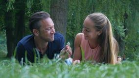 Um par em um parque O indivíduo dá a sua amiga as flores minúsculas que apenas escolheu do gramado video estoque