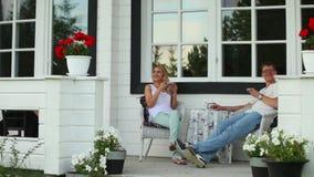 Um par está bebendo o chá no quintal de uma casa de verão vídeos de arquivo