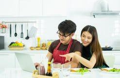 Um par está usando o portátil ao comer o café da manhã na cozinha fotografia de stock royalty free