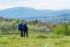 Um par está viajando com as trouxas através do campo fotos de stock royalty free