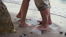 Um par est? andando ao longo da praia em um dia ensolarado claro Guardam as m?os e o beijo Os pés dos homens e das mulheres no vídeos de arquivo
