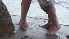 Um par est? andando ao longo da praia em um dia ensolarado claro Guardam as m?os e o beijo os p?s do passeio dos homens e das mul video estoque