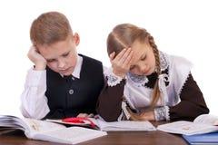 Um par estudantes da escola primária sentam-se em uma mesa Fotografia de Stock Royalty Free