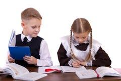 Um par estudantes da escola primária sentam-se em uma mesa Foto de Stock Royalty Free