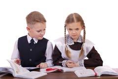 Um par estudantes da escola primária sentam-se em uma mesa Fotos de Stock Royalty Free