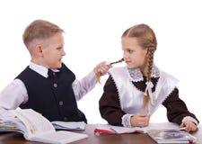 Um par estudantes da escola primária sentam-se em uma mesa Foto de Stock
