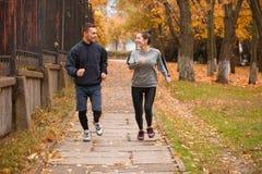 Um par feliz que corre em um outono estaciona outdoors fotos de stock royalty free