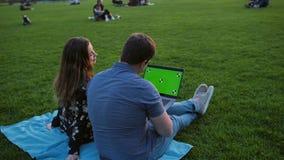 Um par feliz usando o portátil Apronte seguindo vídeos de arquivo