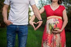 Um par grávido feliz feito das mãos feitas de um coração imagem de stock royalty free