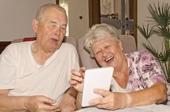 Um par idoso aprecia o Internet na tabuleta fotos de stock royalty free