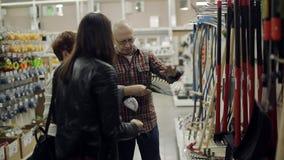 Um par idoso com filha adulta em um supermercado do hardware escolhe o ancinho vídeos de arquivo