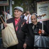 Um par idoso com retratos de um parente participa no regimento imortal o 9 de maio de 2016 em Ulyanovsk, Rússia foto de stock
