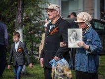 Um par idoso com um retrato de um parente participa no regimento imortal o 9 de maio de 2016 em Ulyanovsk, Rússia fotos de stock