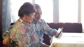 Um par idoso comunica-se com seu neto pelo vídeo que liga a tabuleta Um homem e uma mulher estão falando a filme