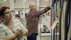 Um par idoso em um supermercado do hardware escolhe o ancinho video estoque
