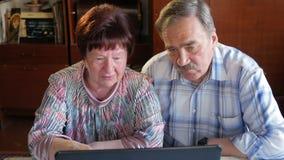 Um par idoso está sentando-se em casa no portátil Uma mulher lê a notícia, um homem com um bigode senta-se ao lado dele e fala-se vídeos de arquivo