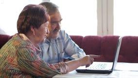 Um par idoso está sentando-se em casa no portátil Uma mulher lê a notícia, um homem com um bigode senta-se ao lado dele e fala-se filme
