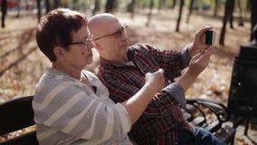 Um par idoso no parque do outono em um banco que toma imagens de mim mesmo no smartphone filme