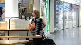 Um par idoso que vem a um café na área de espera do aeroporto migra video estoque