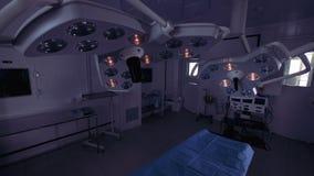 Um par lâmpadas cirúrgicas que penduram acima da tabela de operação estão obtendo ligaram filme