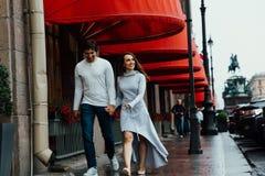 Um par loving abraça sob o dossel vermelho da loja na rua embrace fotografia de stock