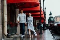 Um par loving abraça sob o dossel vermelho da loja na rua embrace imagens de stock