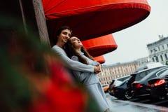 Um par loving abraça sob o dossel vermelho da loja na rua embrace foto de stock royalty free