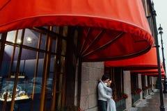 Um par loving abraça sob o dossel vermelho da loja na rua embrace fotos de stock