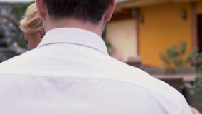 Um par loving sai de um restaurante um homem põe seu revestimento sobre uma senhora O homem está andando abraçando sua mulher Con vídeos de arquivo