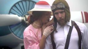 Um par loving, uma mulher em um vestido abraça e afaga ao ombro de um piloto masculino farpado, movimento lento vídeos de arquivo