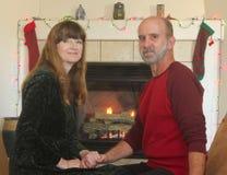Um par na frente de uma chaminé no Natal Fotos de Stock Royalty Free