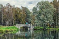 Um par na ponte no lago de prata em Gatchina imagem de stock